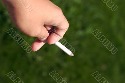 a hand holding a cigarettes