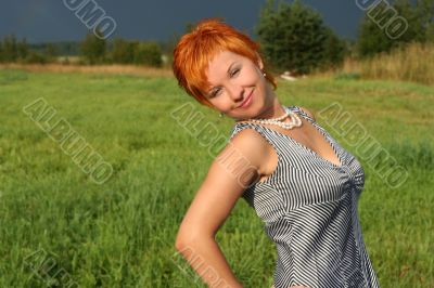 red-haired beautiful woman in dress in field