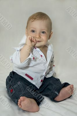 Six-month-old tot sits on shone-gray background