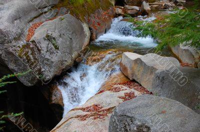 water falls over granite boulders
