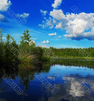 evening lake, clouds are reflected in water