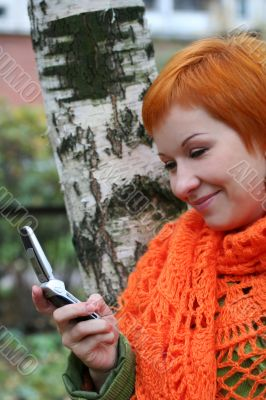 young red-haired woman in red scarf is sms in mobile-phone