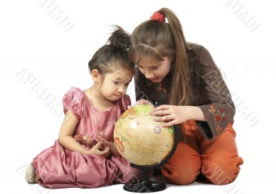 Two girls consider globe