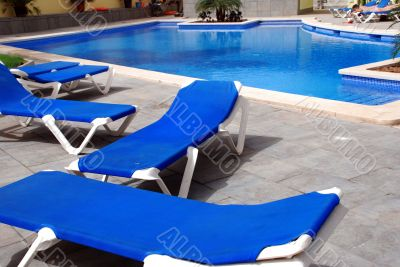 pool with blue chairs around it