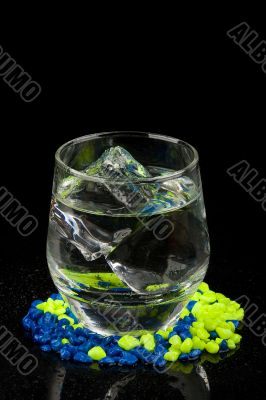Glass with ice and water on gravel