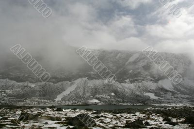 snow mountain in fog with cold lake