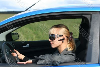 young blond woman in a blue car in sun-glasses with hands free bluetooth