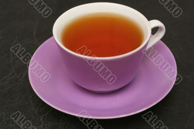 Lilac cup with tea on a black background