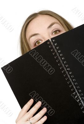 studying peeping over notebook