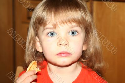 Little pretty blond girl eating pancake