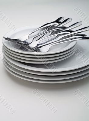Silverware on a stack on white plates