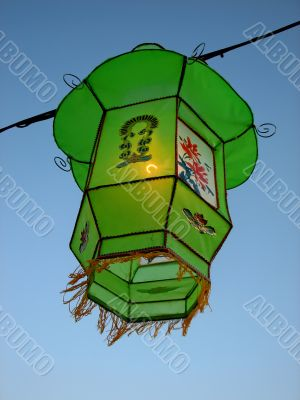 Cozy light of a green Chinese lantern