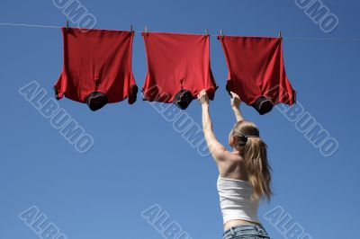 Girl, blue sky and red laundry