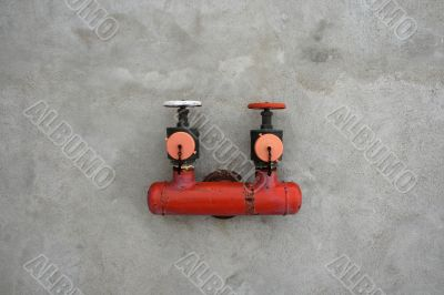Red iron valve on a cement wall