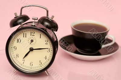 The black alarm clock and black cup from coffee