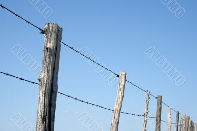 Barbed wire farm fence against blue sky