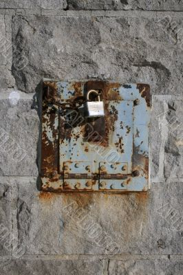Iron lock and rusty chain on a stone wall