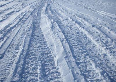 Car tracks crossing the snowy terrain