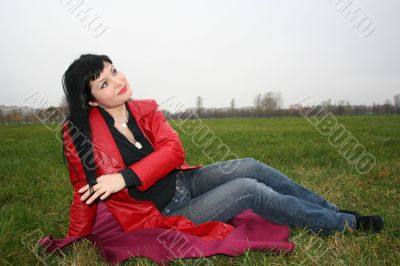 black head woman is sitting on a Plaid in park grass