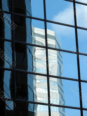 Corporate tower reflecting another office building and the sky