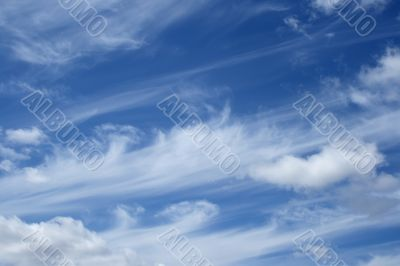 Curly white clouds in the blue sky