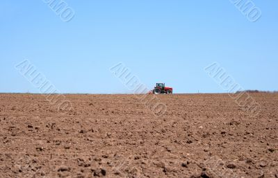 Tractor in a spring field plowing land