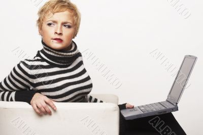 Nice blondgirl sitting on the chair with laptop