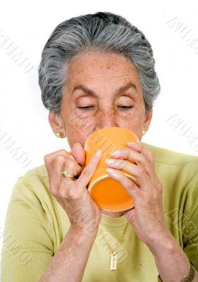 elderly woman drinking a hot drink