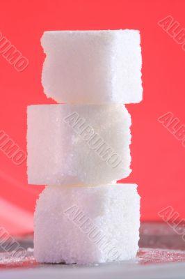 3 sugar cubes on pink