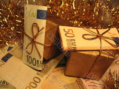 Two golden christmas gift boxes with money