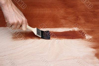Man`s hand painting a wooden surface