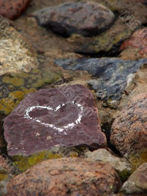 Heart sign drawn on a stone of a river shore.
