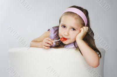 Nice young girl in pink on light background with lollipop