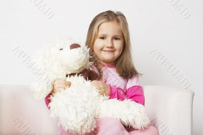 Nice young girl in pink on light background with teddy bear