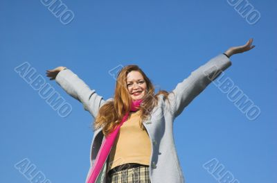 The happy girl on a background of the blue sky