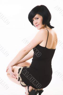 The sitting beautiful brunette in black linen