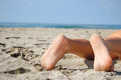 close up of bare feet on beach