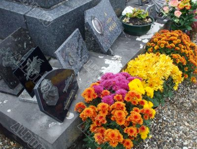 In a cemetery, a gravestone decorated with flowers in autumn