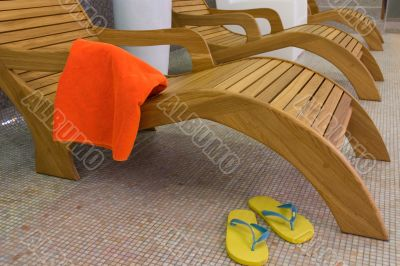 sunbed with orange towel with sandals