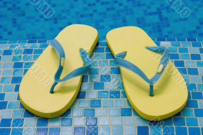yellow sandals on the blue coast of pool