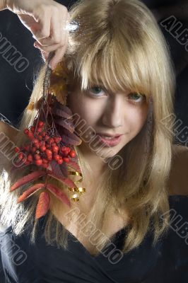 young blonde girl holds a branch of a mountain ash