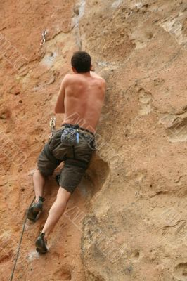 Bare back climber clinging to rock face