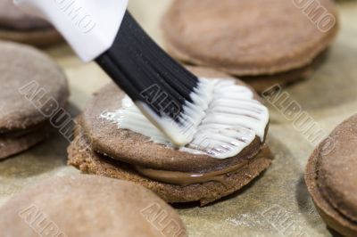 brushing frosting on cookies