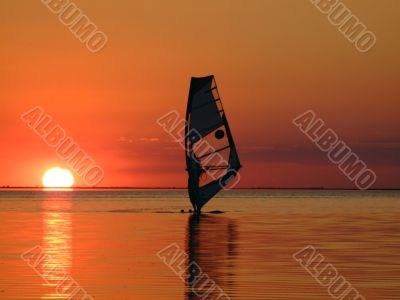 Silhouette of a windsurfer on waves on a sunset 2