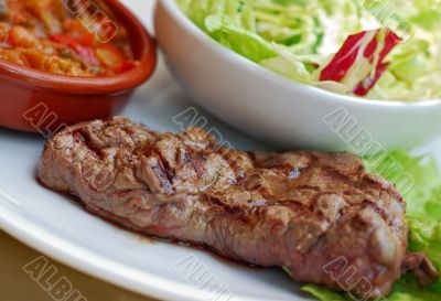 Beef steak blue with salad and ratatouille