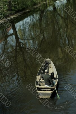Man and dog  in boat on river