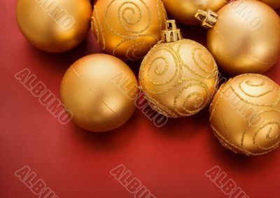 gold christmas baubles on red