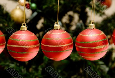christmas baubles with tree in the background