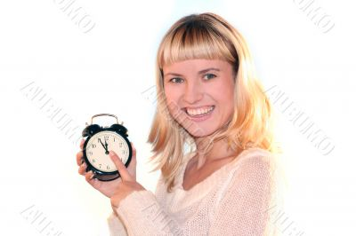 Young blond woman show time on alarm clock. The shot like concept of eve xmas or end of sales