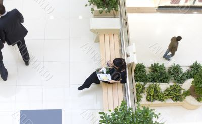 Girl sitting on bench and reading a magazine in a mall
